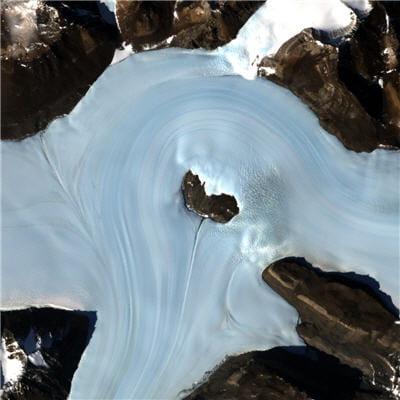 le glacier s'écoule vers la périphérie à cause de la gravité et du poids de la