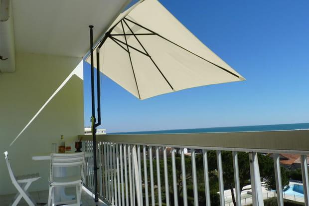 Un parasol de balcon avec pied inclinable et télescopique
