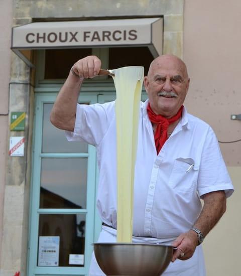 L'Aveyronnais  - Le chef en train de filer l'Aligot devant le restaurant -   © Julien