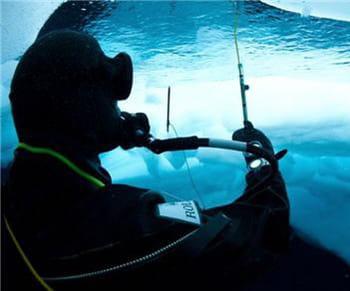 le plongeur mesure l'épaisseur de la glace sous l'eau.